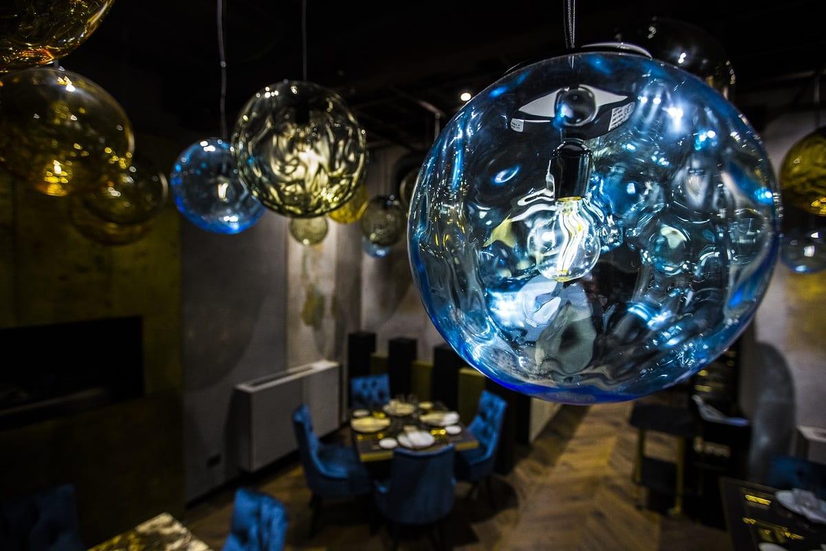 La sala di Antica Fonderia con i lampadari in vetro di Murano oro e blu