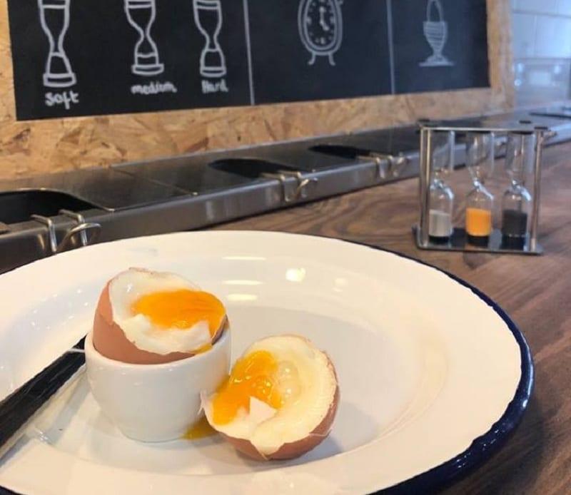 Un uovo sodo nel piatto sulla mensola di Eggs&Bread e la lavagna con le istruzioni per l'uso