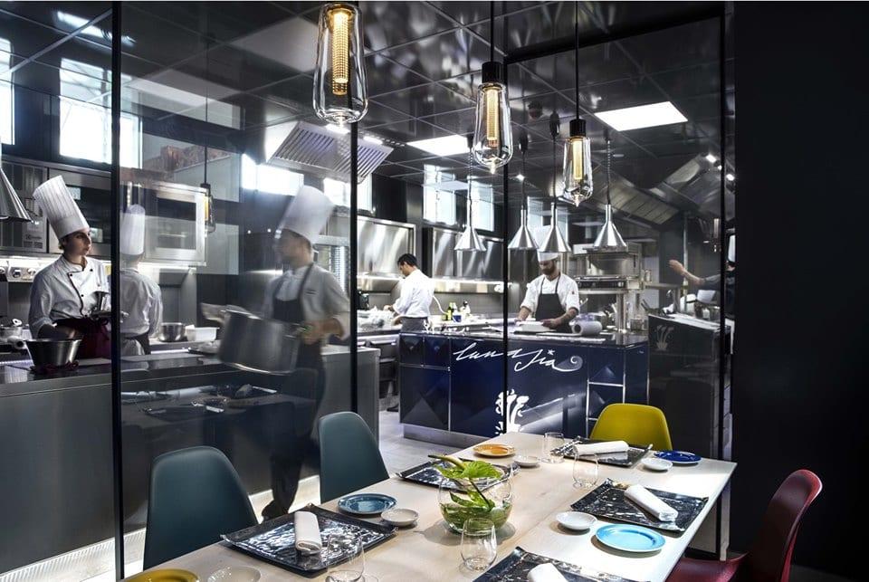 La cucina del ristorante Lunasia vista dalla sala attraverso una parete vetrata