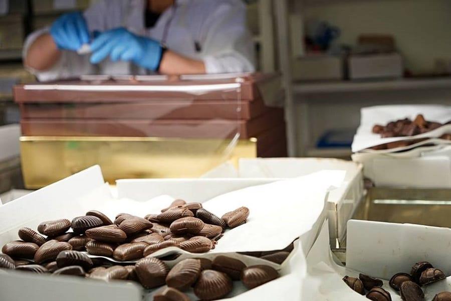 Peyrano: nel laboratorio del cioccolato di Peyrano, con cioccolatini in primo piano e mani al lavoro sullo sfondo