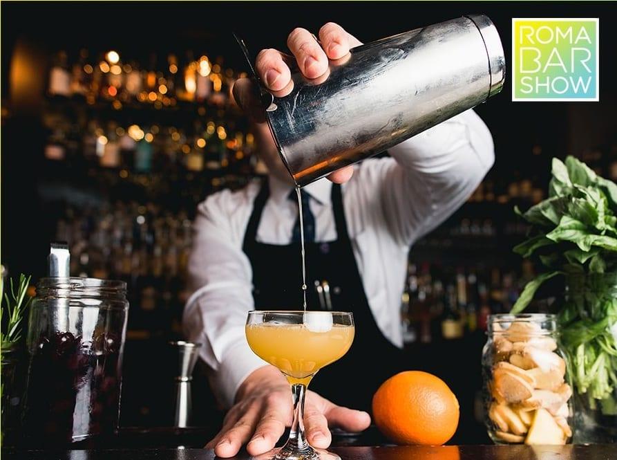 Un barman completa un cocktail versandolo in coppa Martini dallo shaker