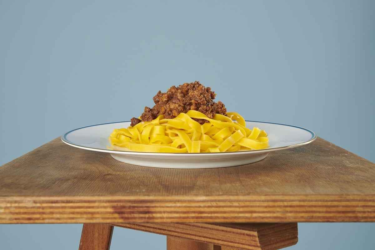 Un piatto di tagliatelle all'uovo con ragù alla bolognese su tavolo in legno