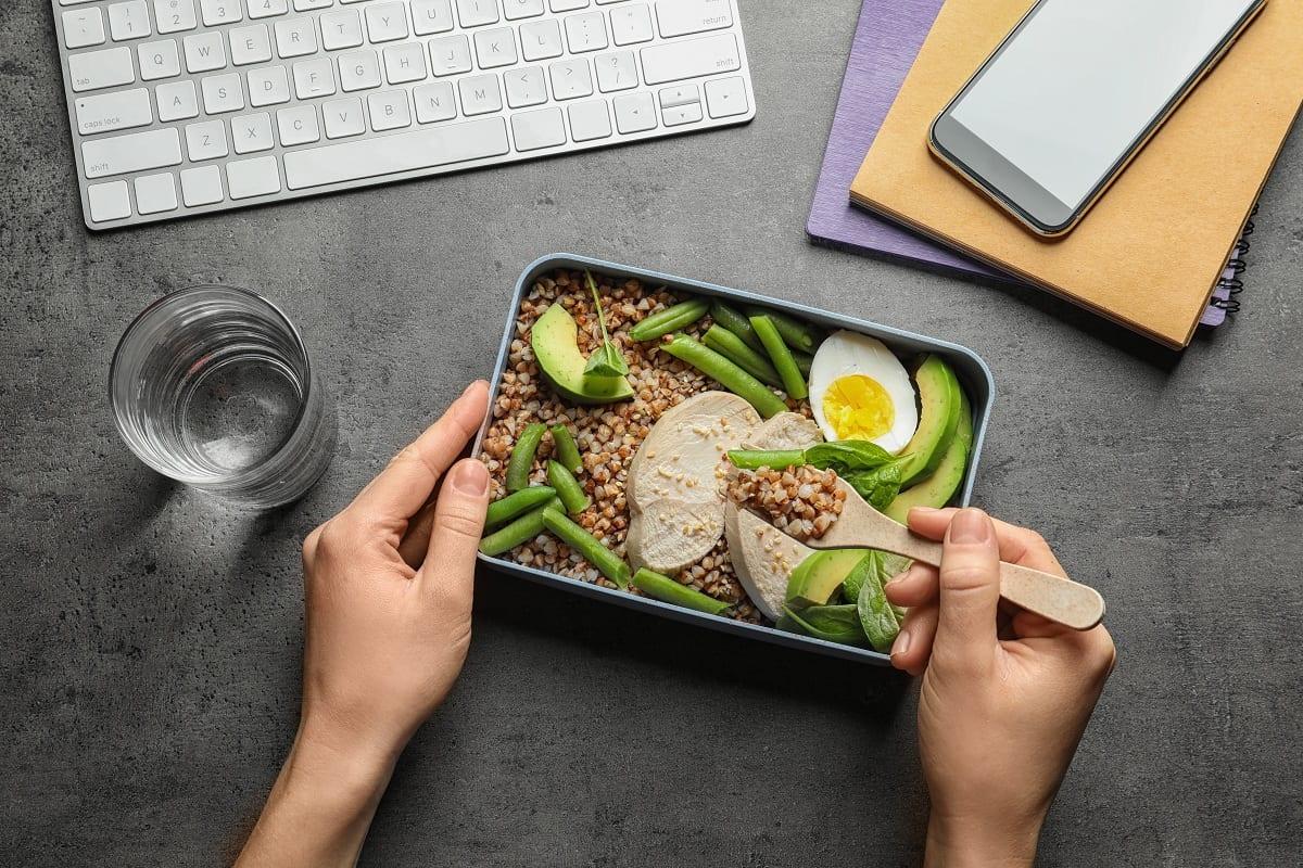 Lunch box con insalata di farro, fagiolini e avocado da mangiare alla scrivania, davanti al pc