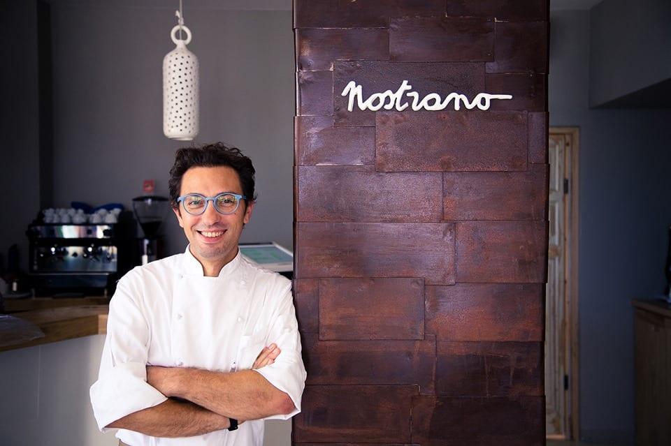 Stefano Ciotti ritratto in giacca da chef nel suo ristorante Nostrano
