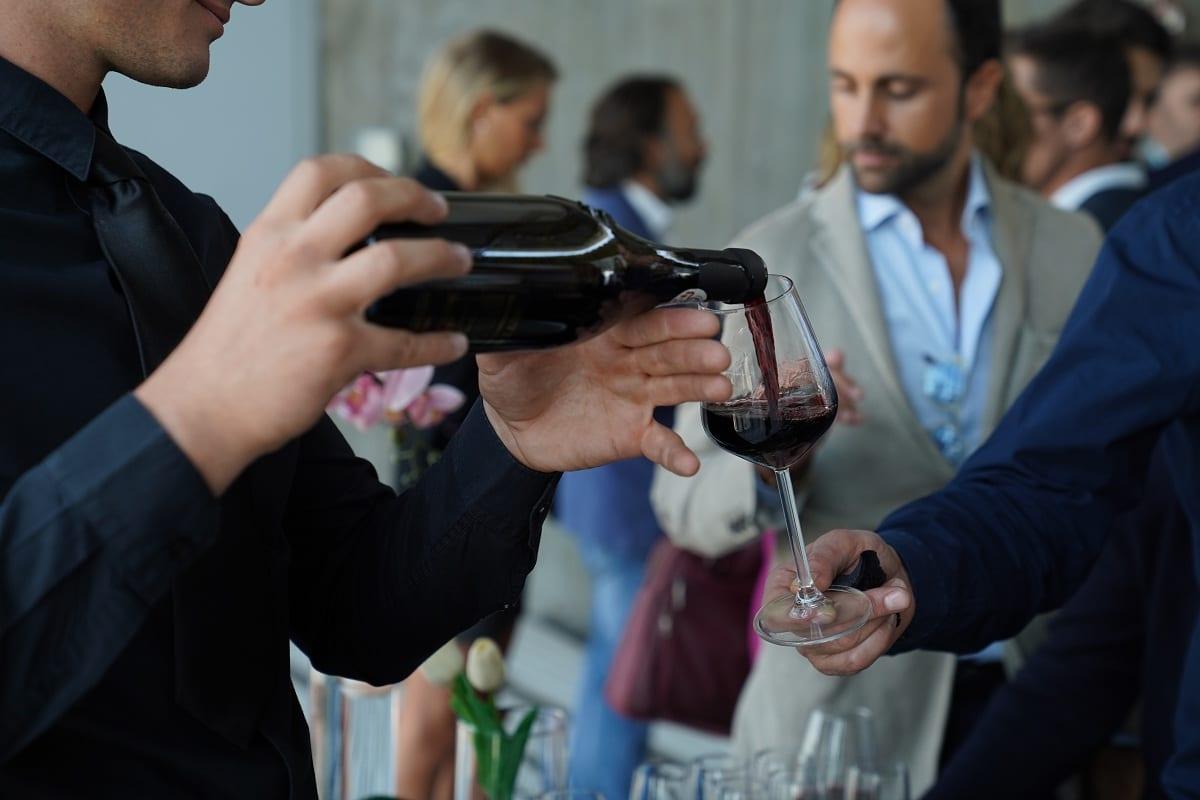 Banchi d'assaggio vino, con bottiglia di vino rosso
