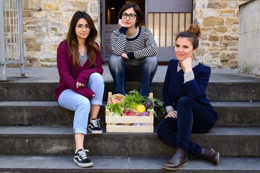 Il team di Genuino.Zero: tre ragazze e una cassetta di frutta e verdure sulle scale di ingresso alle Murate