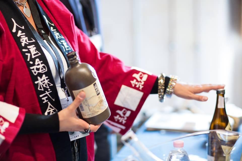 Una donna in abito giapponese serve sake in bottiglia