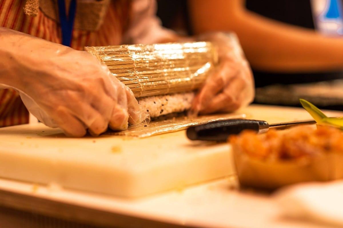 Preparazione del sushi con il tappetino in bambù per compattare il riso