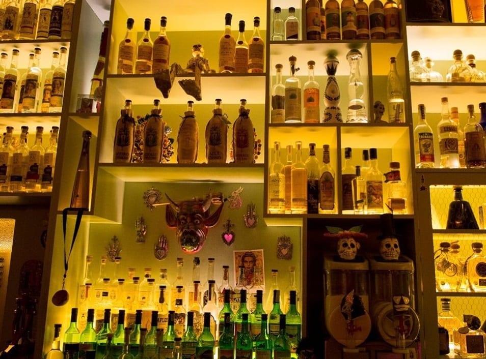 La parete con bottiglie di mezcal e tequila a La Punta di Roma
