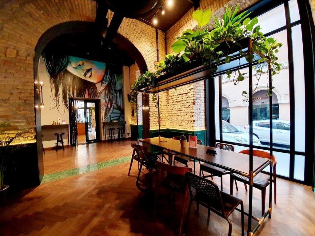 Il bar dell'Hotel Chapter, con archi in mattoncini, murale, piante sospese