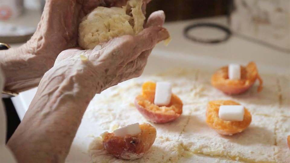 Mani di una nonna in cucina con l'impasto per un dolce alle albicocche