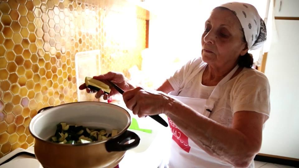 Una nonna ai fornelli, nella sua cucina, mentre taglia le zucchine
