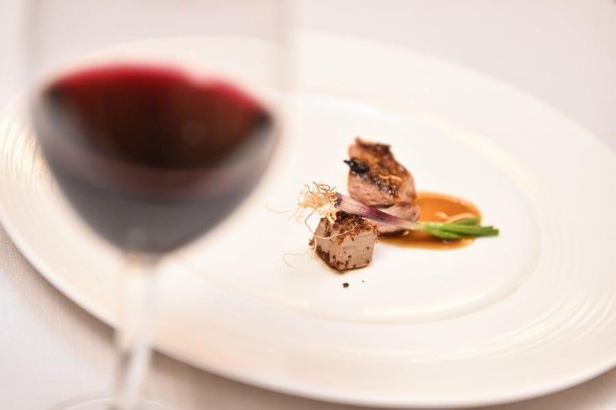Un piatto di carne e calice di lambrusco sfumato in primo piano