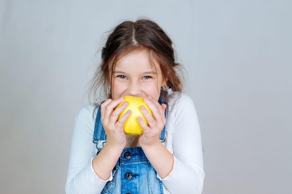 Una bimba di 7 anni addenta una mela gialla e sorride