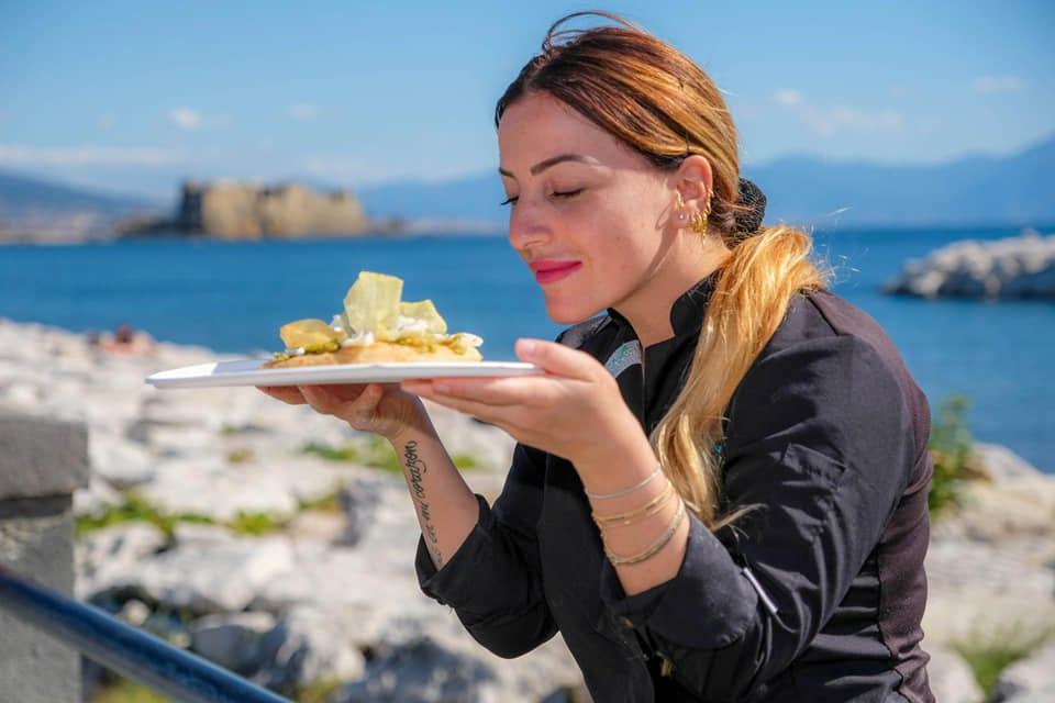 Isabella De Cham con un piatto di pizza fritta, sul lungomare di Napoli