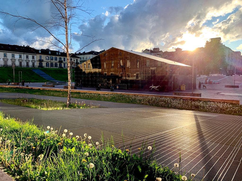 Piazzale Fusi e l'edificio di Open Baladin, mentre spunta il sole dalle nuvole