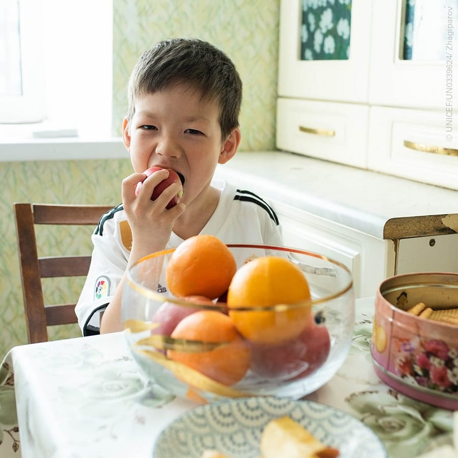 Un bambino addenta una mela nella cucina di casa, con fruttiera di arance e mele