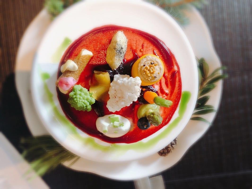 Un piatto gourmet vegetale con gazpacho di pomodoro e ortaggi