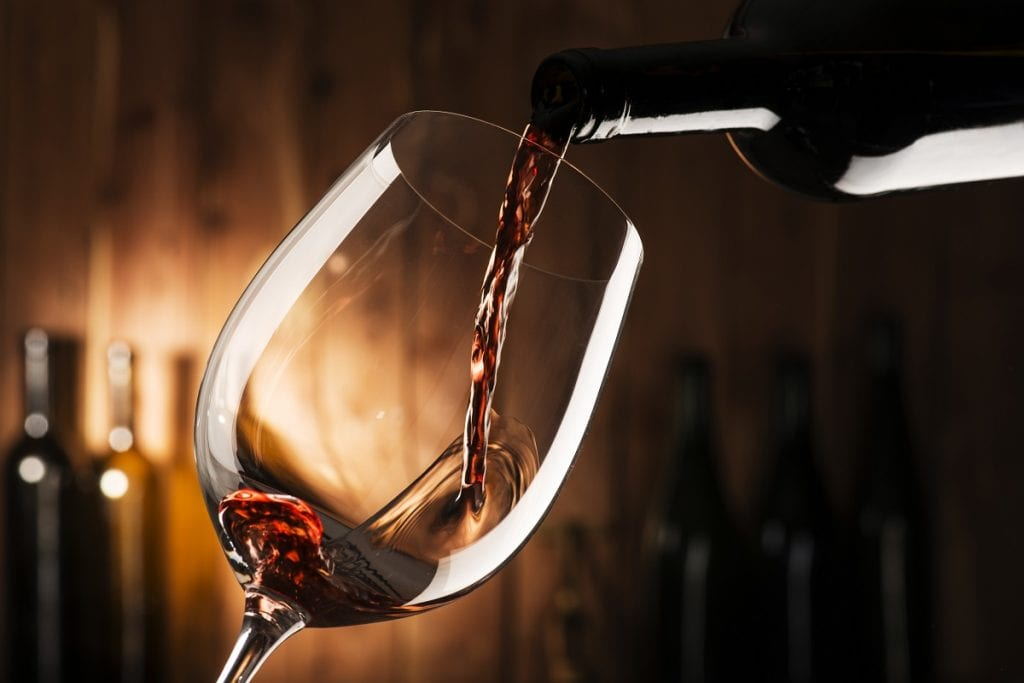 Un calice di vino rosso versato dalla bottiglia