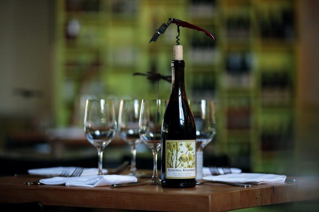 Una bottiglia di vino rosso e quattro calici su un tavolo apparecchiato