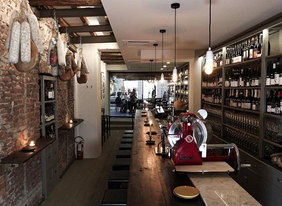 Il banco con bottigliera e salumi appesi al soffitto di ASVN a Milano