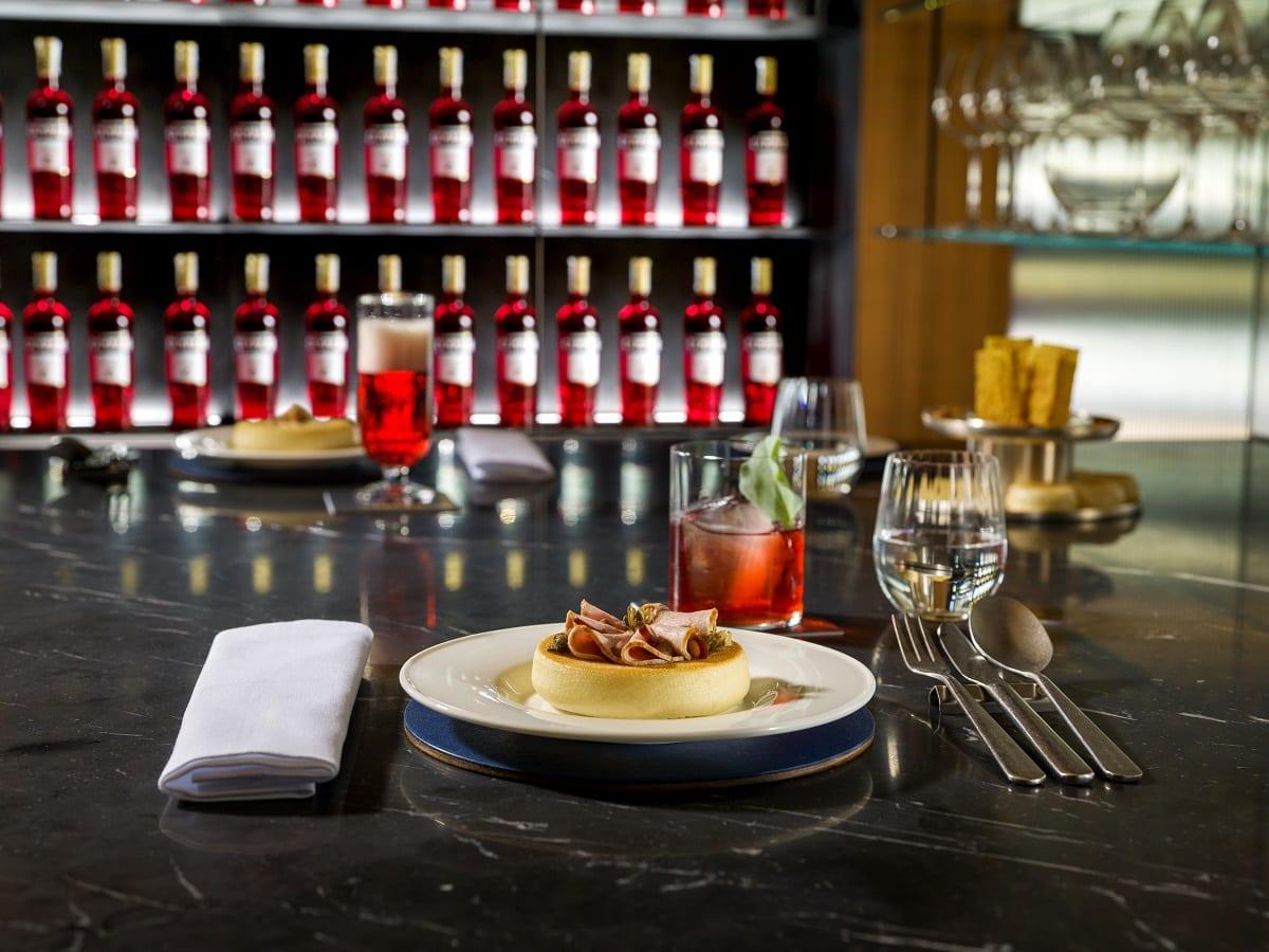 Pancotto servito al piatto in Sala Spritello, con parete di bottiglie Campari al Camparino