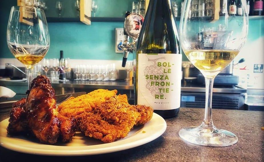 Pollo fritto al piatto e calice di vino naturale, con bottiglia da Pastella
