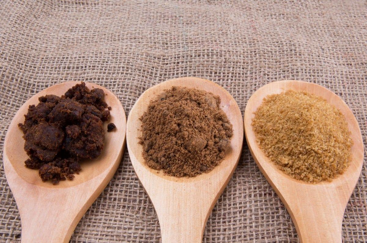 Zuccheri tipologie Muscovado sugar, brown sugar and coconut sugar in wooden spoon