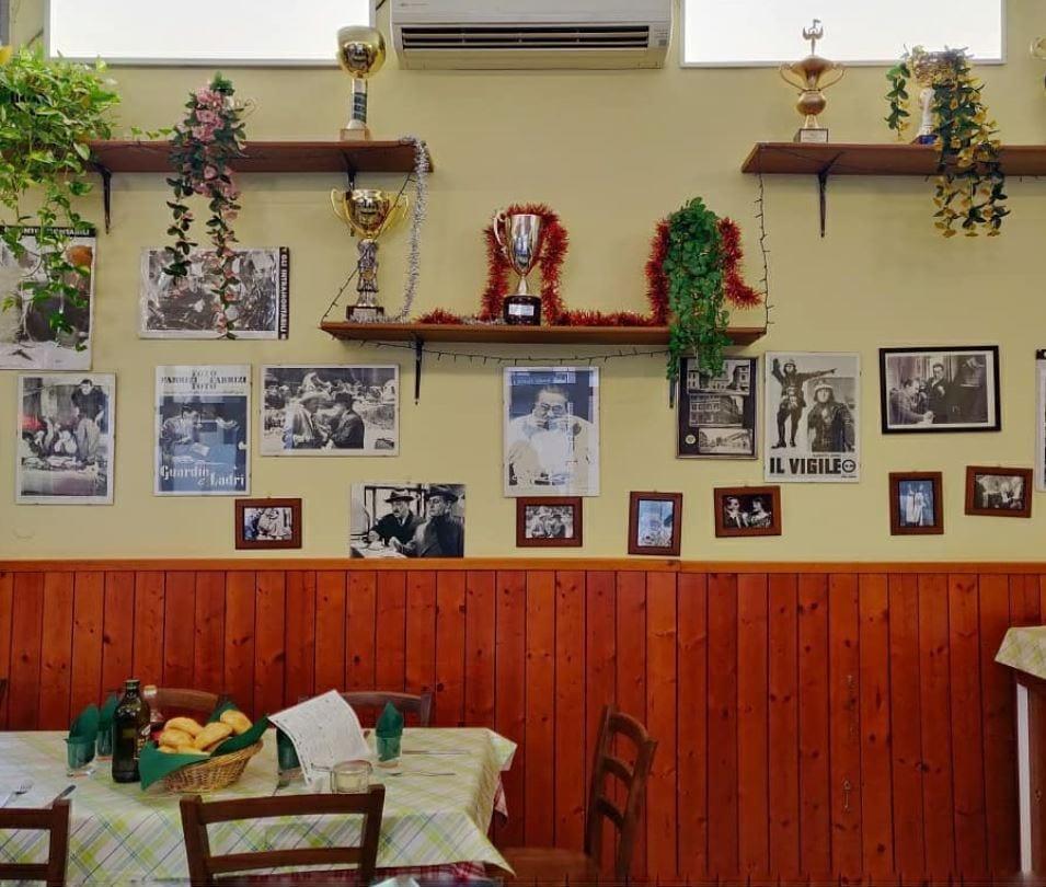 Iconografia di una vecchia trattoria: foto in bianco e nero, trofei, boiserie in legno, tavola apparecchiata