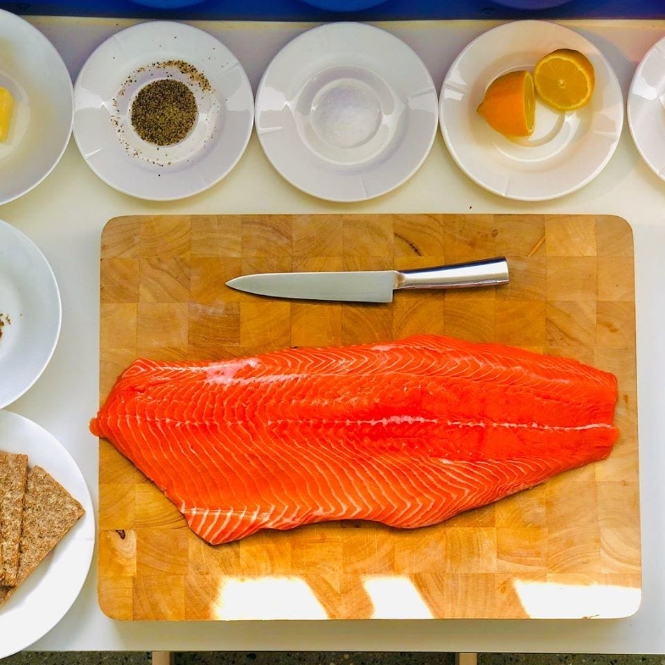 Filetto di salmone su tagliere con ciotole di aromi e limone