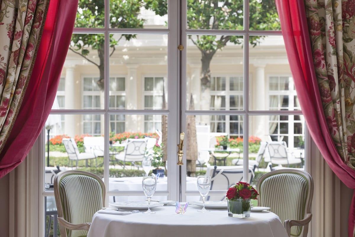 Un tavolo a L'Epicure di Parigi, affacciato sul giardino dell'hotel Bristol