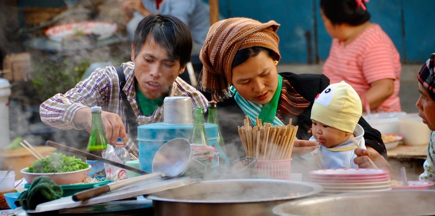 Una famiglia asiatica mangia a una tavola popolare, in strada