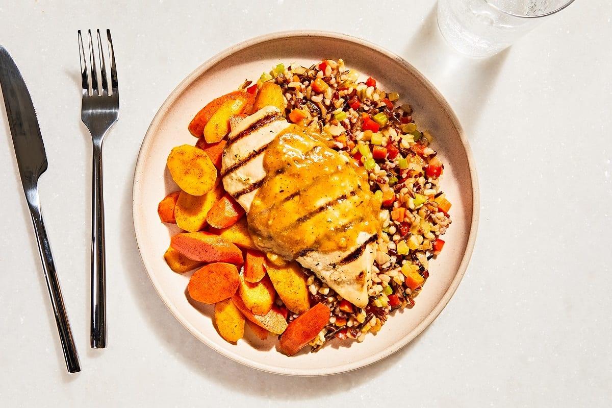 Un piatto di pollo alla griglia e carote con salsa