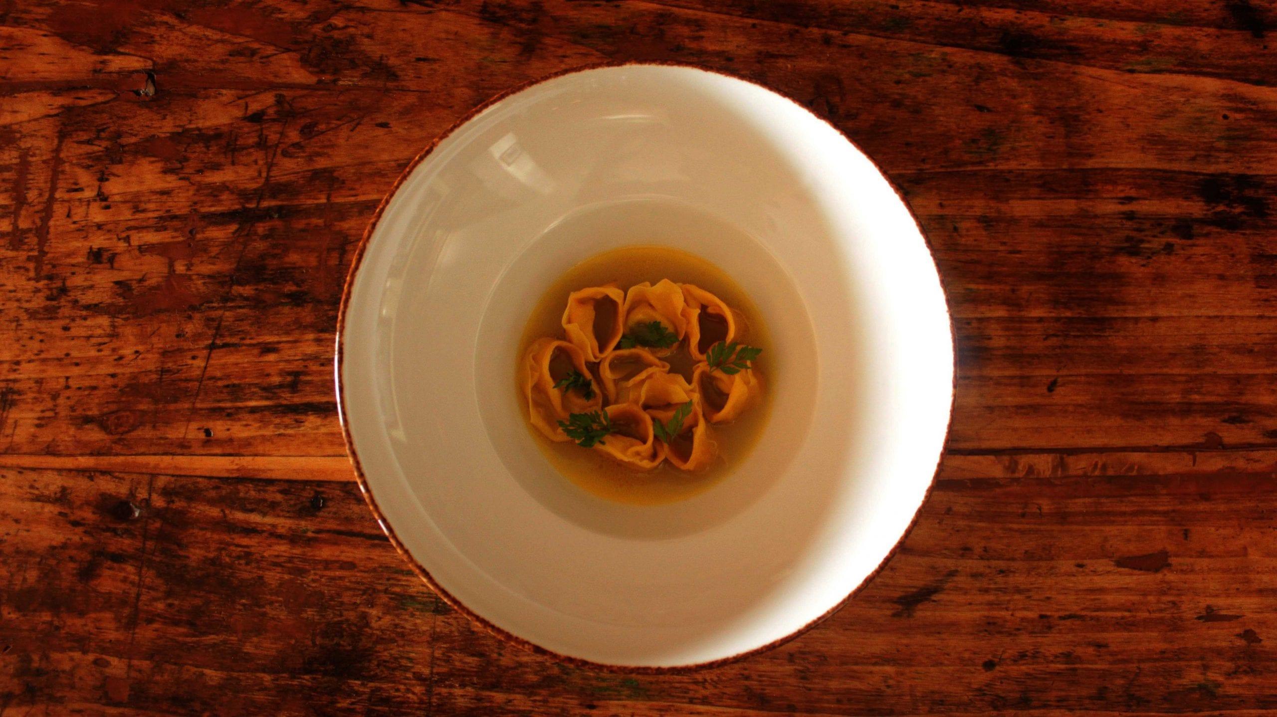 Cappelletti con ripieno di cavolo cappuccio alla brace fermentato in brodo di pollo e miso di caffè verde