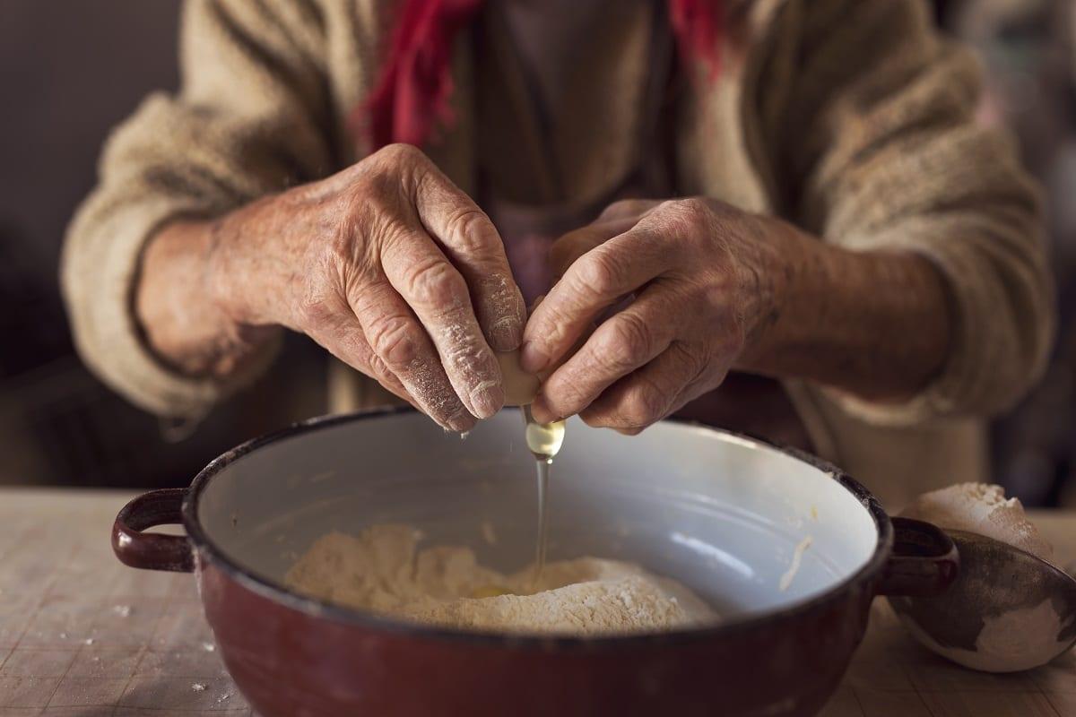 Due mani anziane rompono delle uova nella farina
