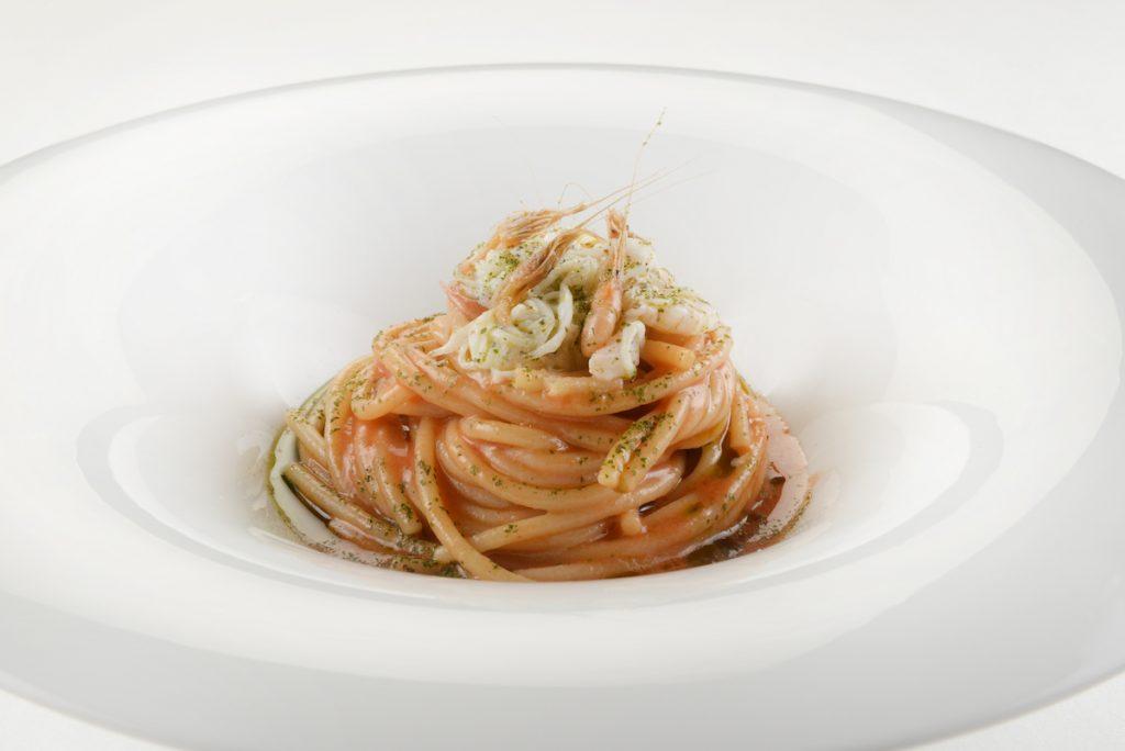 Spaghetti martelli cotti in estrazione di crostacei crudo di novellame di pesce e alloro
