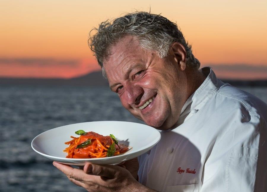 Peppe Guida che tiene un piatto di pasta