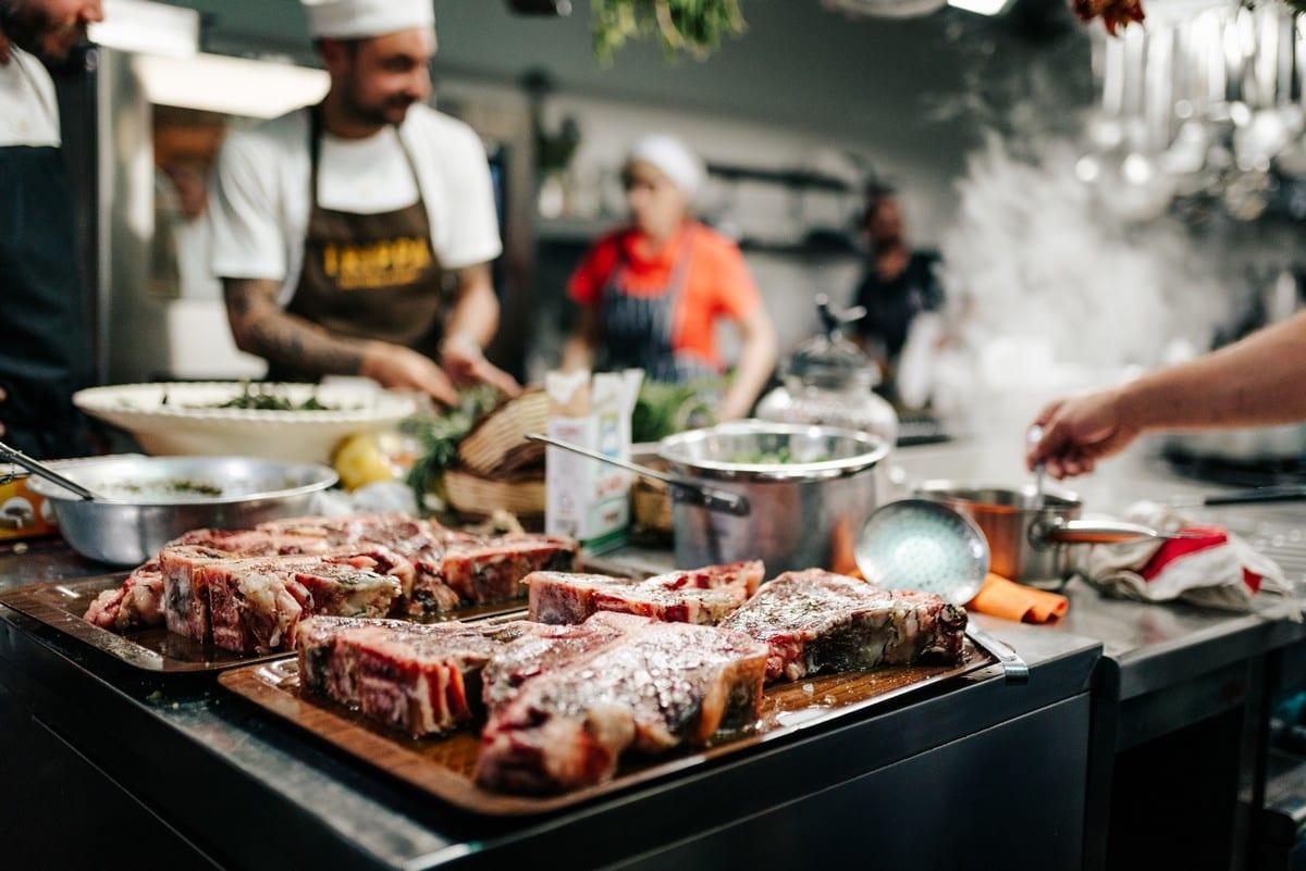 La cucina di NoMenu, con gli chef all'opera e la carne pronta per la cottura in primo piano