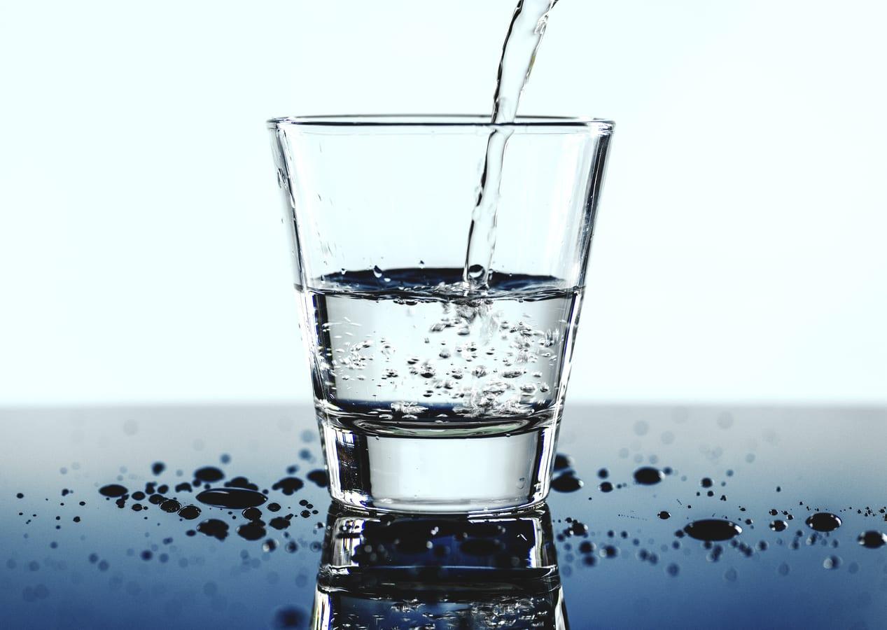 Bicchiere di acqua friante mentre viene riempito
