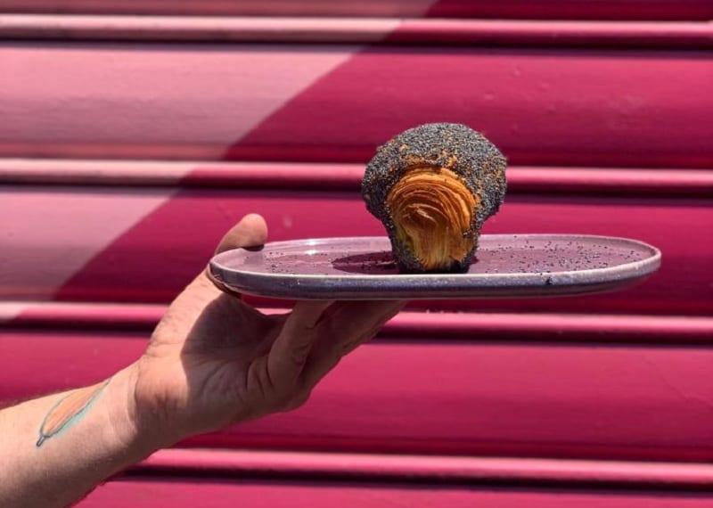 Brioche con semi di papavero al piatto, con saracinesca fucsia sullo sfondo