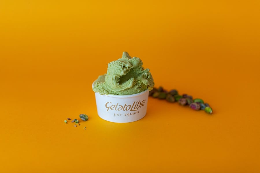 Una coppetta di gelato al pistacchio su fondo arancione
