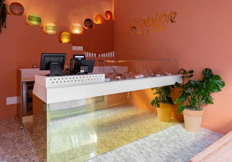 L'interno della gelateria Gelato Libre a Milano, con bancone dorato, pareti rosa e piatti in vetro colorato, pavimento a mosaico in tessere di marmo