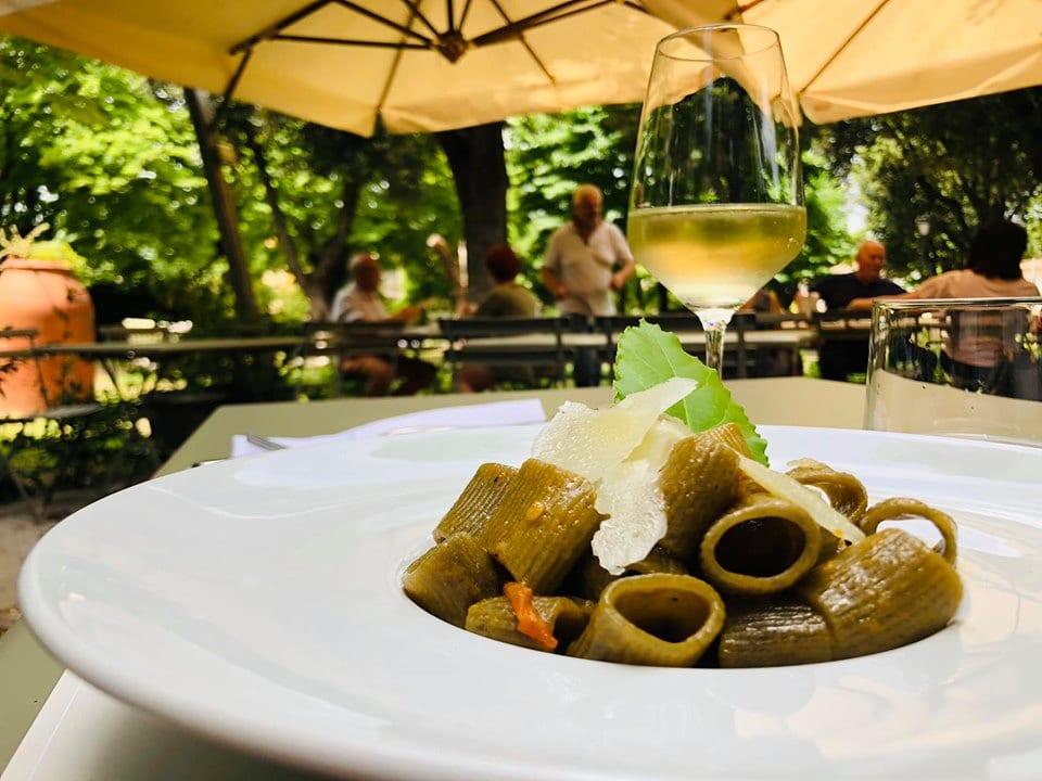 Piatto di pasta con calice di vino alla trattoria umbra Le Delizie del Borgo, Bevagna