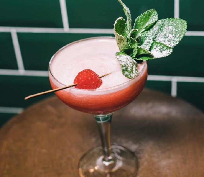 Un cocktail in coppa Martini con lampone e menta