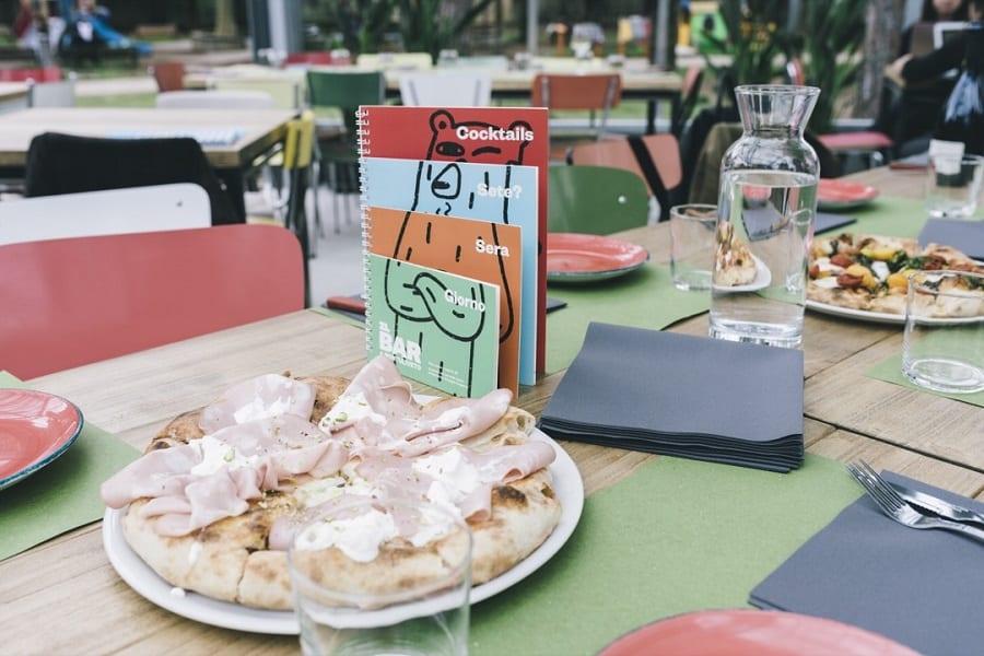 Il tavolo del ristorante Montuliveto, con i menu e la pizza in tavola