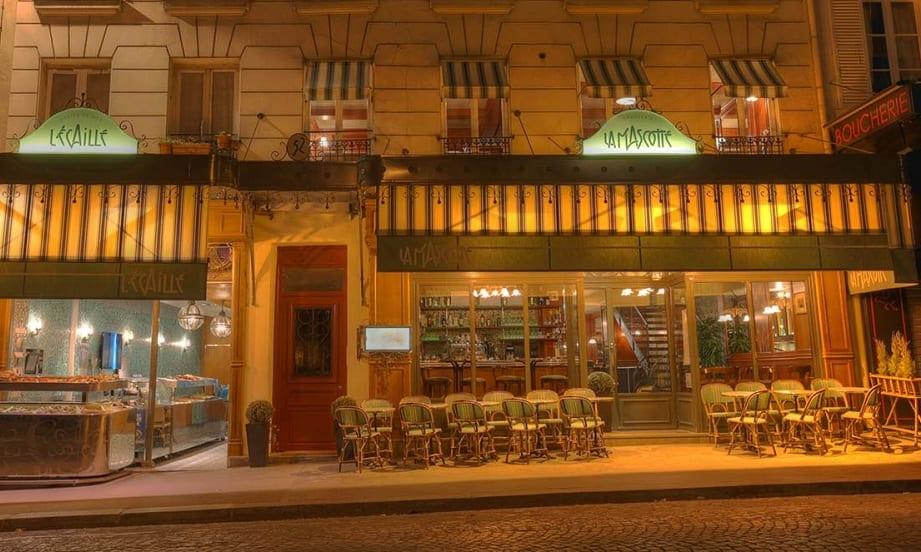 L'esterno di un bistrot parigino, di notte, con i tavoli su strada e la tenda a righe
