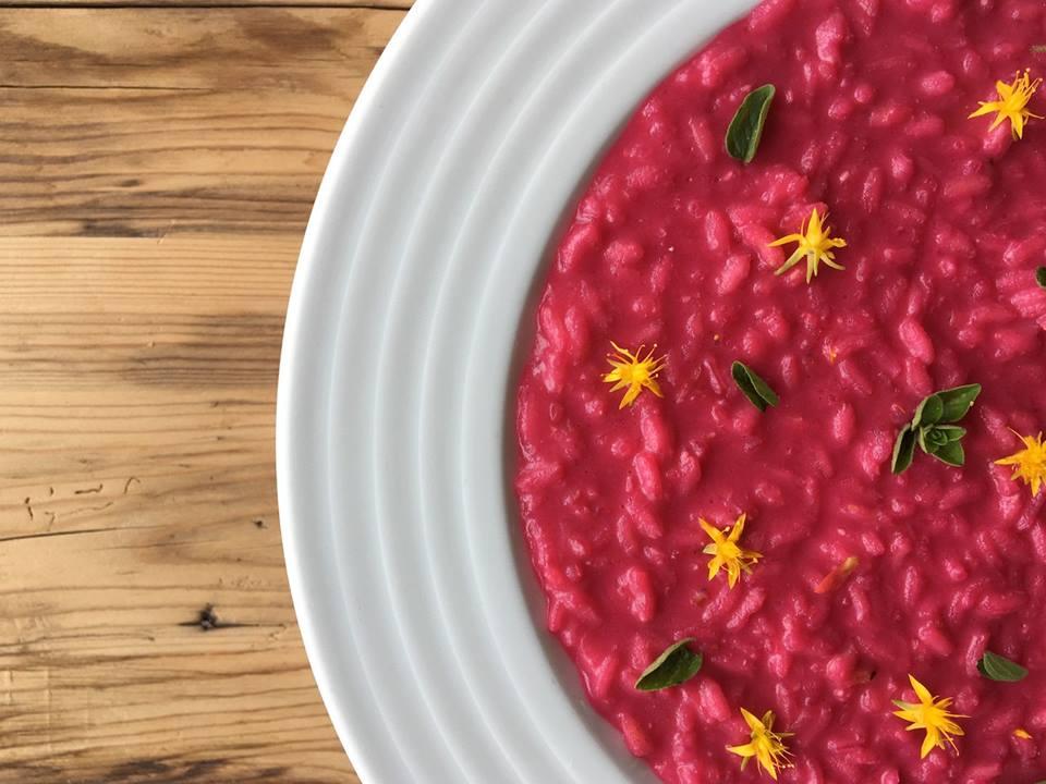 Un piatto di risotto alla rapa rossa su tavolo in legno, fotografato a metà