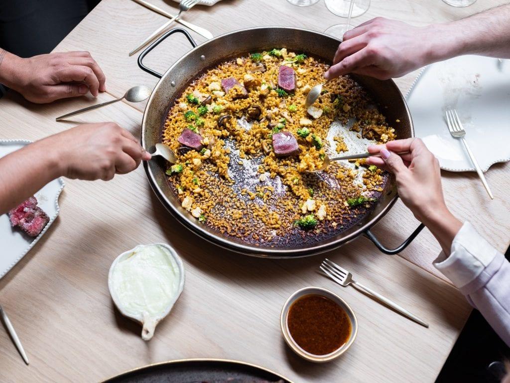 Una paella con riso al centro del tavola condivisa da più commensali