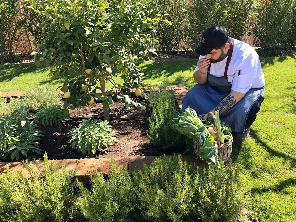 Lo chef nell'orto mentre annusa un'erba aromatica all'Ortoristorante di Pula