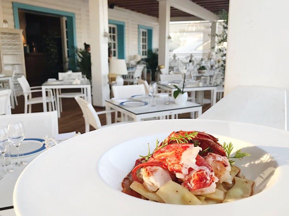 Un piatto di pasta con astice allo Yacht Club di Porto Rotondo con i tavoli bianchi in veranda sullo sfondo